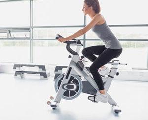 Pige på motionscykel